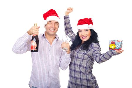 Happy smiling couple in Santa hats holding champagne ,glasses and Christmas gift ,cheering and laughing together isolated on white background photo