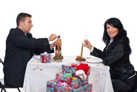Happy couple sitting at Christmas table and man opening  champagne bottle to toasting together Stock Photo - 8042191
