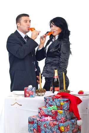 Cheerful couple drinking champagne and standing together near Christmas table with presents  photo