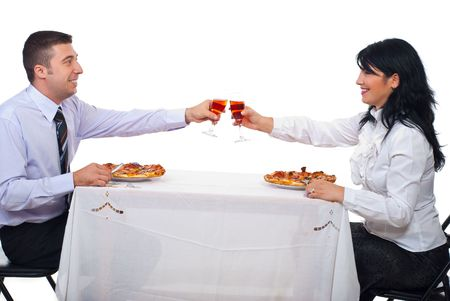 Two business  people  toasting with wine and eating pizza at table photo