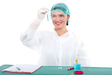 Smiling laboratory woman looking at a tube with blue liquid  photo