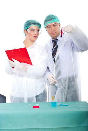 Team of two researchers people examine blood tube and woman taking notes in clipboard in a laboratory photo