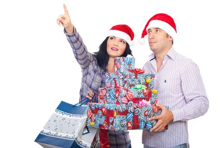 Couple holding shopping bags and Christmas gifts pointing  and looking up somehwere isolated on white background Stock Photo - 8042223