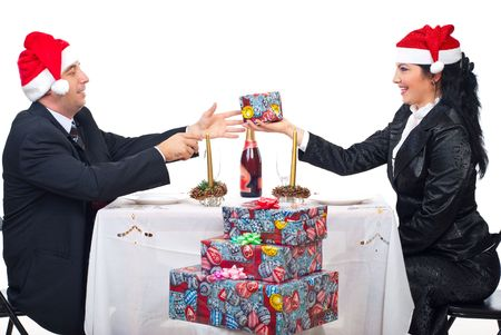 Elegant couple with Santa hats sharing Christmas gift and sitting together at table Stock Photo - 8042220