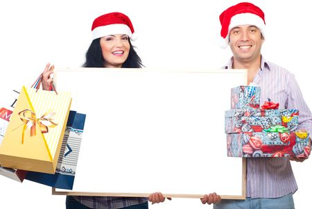 Happy smiling couple with Santa hats holding Christmas shopping bags and gifts boxes and a blank white banner  photo
