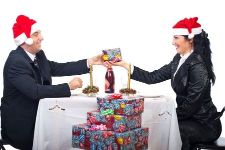 Cheerful laughing couple sitting at Christmas table dinner and sharing gifts isolated on white background photo