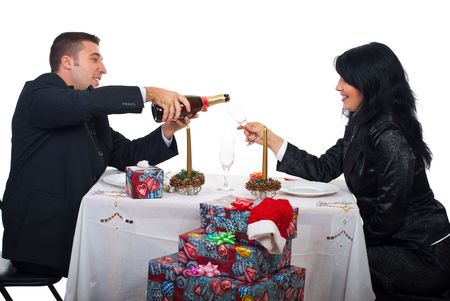 Man pouring champagne in a glass for his wife and preparing to toast  at Christmas table dinner Stock Photo - 8103100