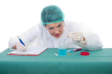 Scientist woman pouring with pipette making experiments and taking notes in her clipboard photo