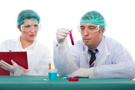 Two scientists working in laboratory,man examine blood tube and woman writing notes in clipboard photo
