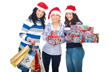 Mother with two daughters wearing Santa hats and holding Christmas gifts isolated on white background photo