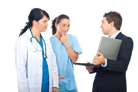 grupo de m�dicos: Hombre de la celebraci�n de un ordenador port�til y tener conversaci�n con dos m�dicos mujeres aisladas sobre fondo blanco  Foto de archivo