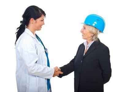 manos estrechadas: Joven doctor mujer y arquitecto senior dando el movimiento de la mano y sonriendo aislados sobre fondo blanco