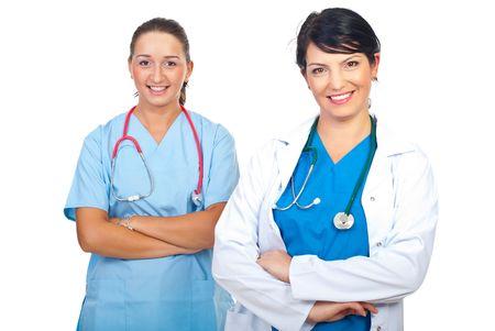 mani incrociate: Due donne attraenti felice medici in piedi con le mani incrociate e sorridente isolati su sfondo bianco