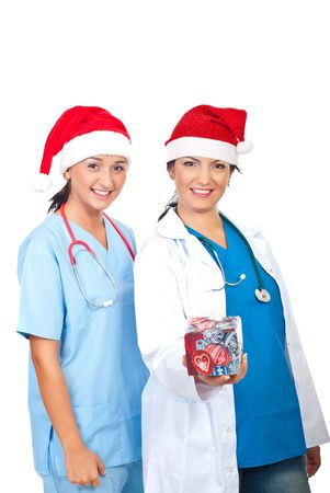 Two young happy doctors women with Santa hats offering a Christmas gift isolated on white background Stock Photo - 8103212