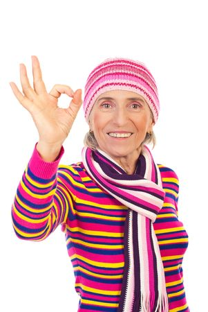 neckcloth: Senior woman in winter knitted clothes showing okay sign hand and smiling isolated on white background