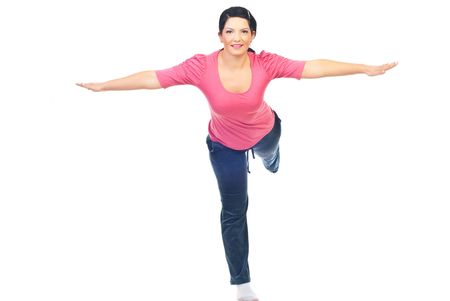 Woman  doing sport and standing in a leg with both hands and one  leg  outstretched isolated on white background photo