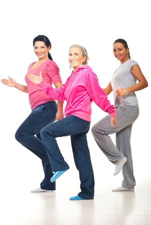 Group of three women doing fitness and smiling over white background Stock Photo