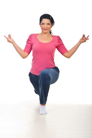 Smiling mid adult woman in yoga position  on floor over white background photo