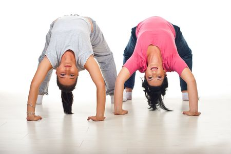 Two flexible women  doing back -bend on floor over white background photo