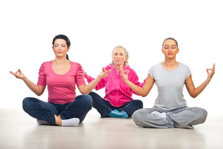 Group of three women in lotus yoga position on floor over white background photo