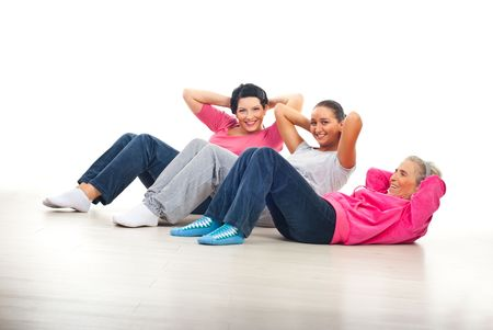 Laughing happy women having fun and doing abs on floor over white background photo