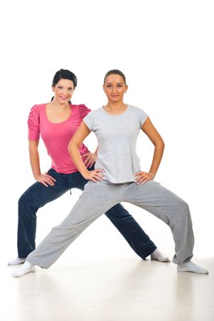Fitness girls  doing exercises and smiling on floor over white background photo