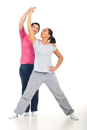Young woman is helped by her personal trainer to making exercises photo