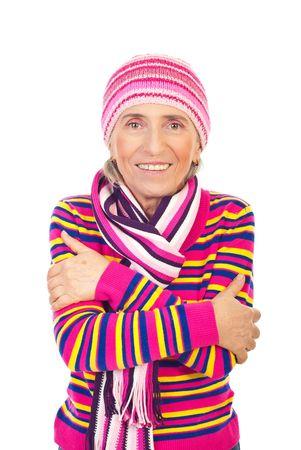 mani incrociate: Bella donna senior sorridente, vestita in abiti maglia rosa, in piedi con le mani incrociate isolato su sfondo bianco