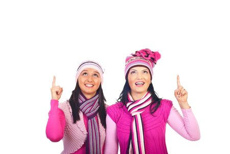 neckcloth: Beautiful happy women with toothy smiles  in pink winter knitted clothes pointing up to copy space isolated on white background