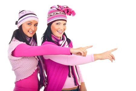 Two winter models  girls in pink clothes pointing to left part of image with copy space isolated on white background photo