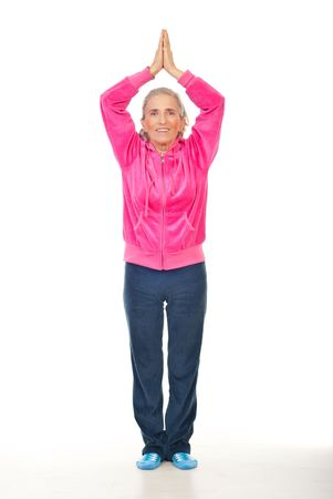 Smiling aged woman in pink sport suit doing yoga over white background photo