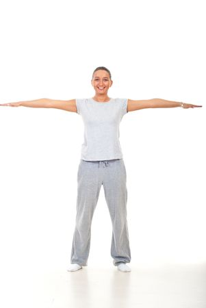 Smiling young woman doing fitness and standing on floor with hands well stretched over white background photo