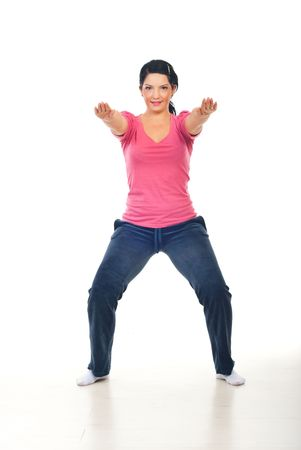 Smiling woman training and doing squats on floor over white background photo