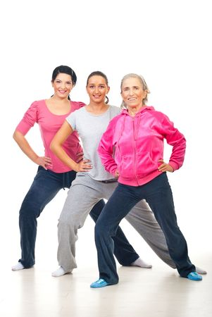 Group of three cheerful women doing fitness over white background Stock Photo