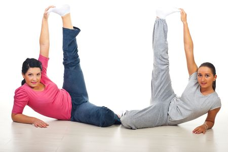 Two active fitness women training  and standing with legs up on floor photo