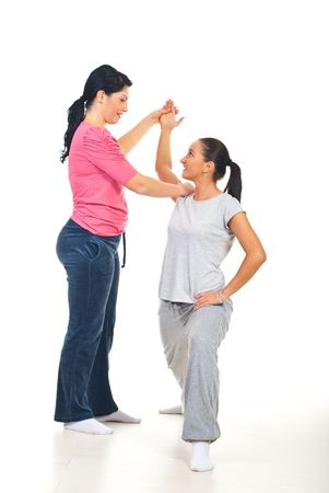 Fitness instructor assisting woman and having conversation together photo