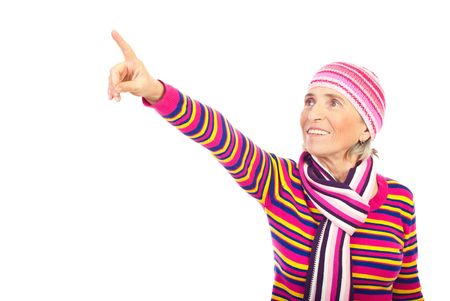 Smiling senior woman in woolen cap pointing away isolated on white background,copy space for text message in left part of image photo