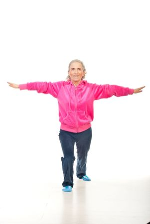 Active senior smiling woman training on floor over white background photo