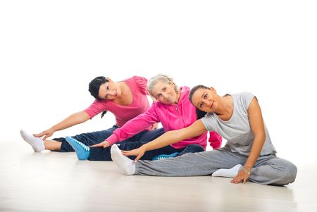 indoor shot: Group of three women training and stretching legs on floor over white background