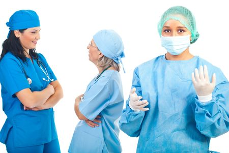Surgeon woman wearing  sterile  uniform with mask,cap and gloves and her team having conversation in background photo