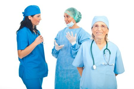 Surgeon senior woman smiling while her young team having conversation in background photo