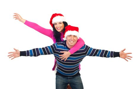 Cheerful couple wearing Santa hats and  the man giving  a piggy back ride to woman and both standing with hands open and smiling isolated on white background photo
