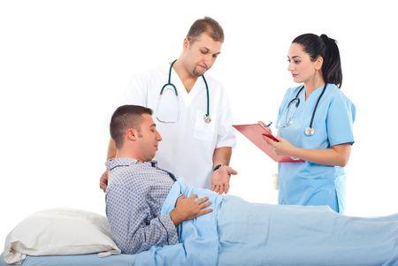 Upset doctor man  having conversation with nurse woman about sick male patient  photo