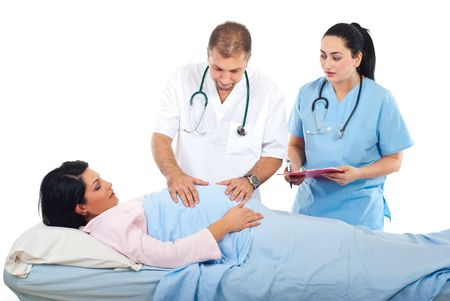 gynecologist: Doctor man holding hands on a pregnant tummy examinating while the nurse talking and holding a clipboard Stock Photo