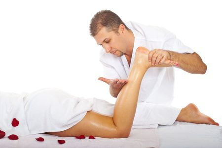 Therapist man massaging womans leg at spa resort photo