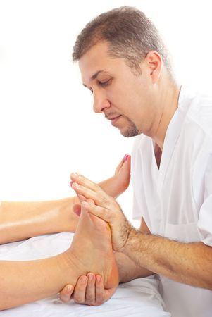Orthopaed man massaging womans foot  and making therapy photo
