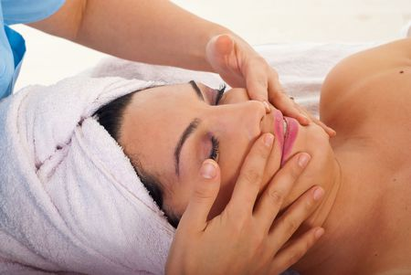 Beautician  giving facial massage to a beauty woman in a spa salon photo