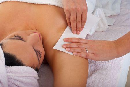 waxen: Schoonheidsspecialiste wassende oksel aan een vrouw in een salon