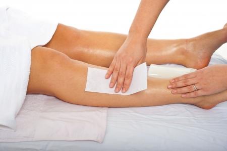 waxen: Schoonheidsspecialist waxing vrouw benen in een salon spa