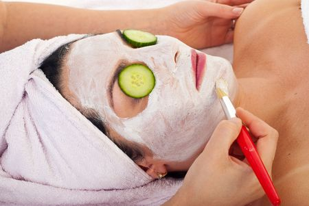 Closeup of beautician applying facial mask and cucumber slices to a woman in a spa salon photo